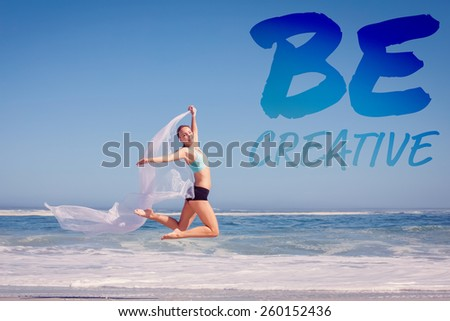 Fit woman jumping gracefully on the beach with scarf against be creative - stock photo