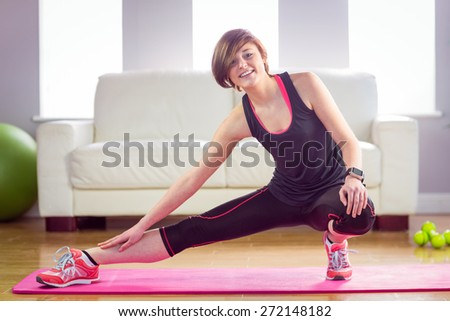 Fit woman looking at camera and stretching on exercise mat at home in the living room - stock photo