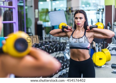 Fit woman looking at mirror, exercising with kettlebell in gym. - stock photo
