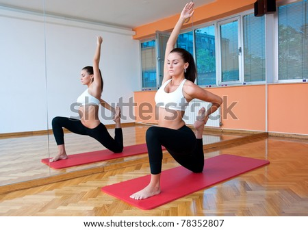 fit woman making stretching exercise in front of fitness studio mirror - stock photo