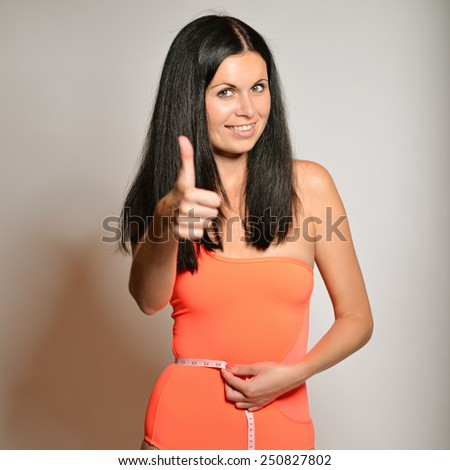 Fit woman measuring her waist. Slim girl with centimeter isolated on white. thumbs up. Fit woman measuring her waist. Slim girl with centimeter isolated on white  thumbs up - stock photo
