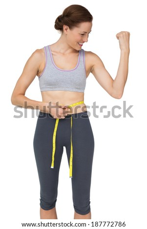 Fit woman measuring waist while flexing muscles over white background - stock photo