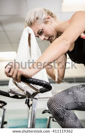 Fit woman on exercise bike wiping sweat with towel at the gym - stock photo