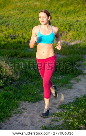 Fit woman running on a path outside - stock photo