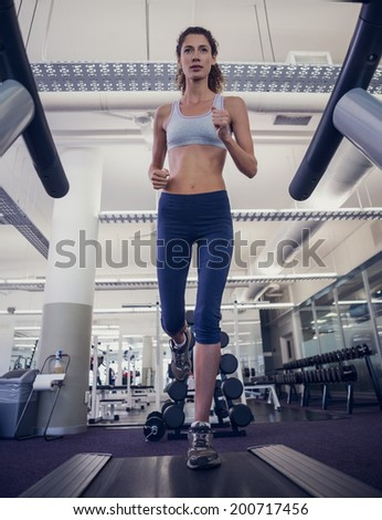 Fit woman running on the treadmill at the gym - stock photo