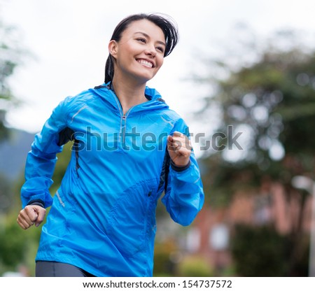 Fit woman running outdoors looking very happy  - stock photo