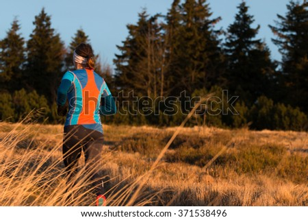 fit woman running up the hill in mountains fitness training in cold autumn morning - stock photo