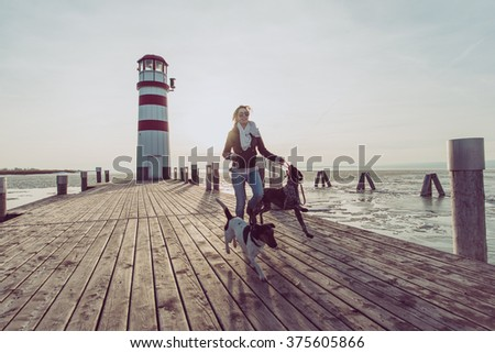 Fit woman running with dogs - stock photo