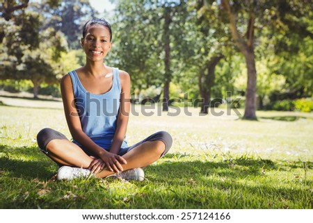 Fit woman sitting in the park on a sunny day - stock photo
