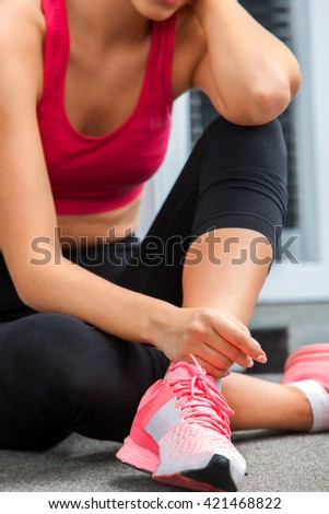 Fit woman sitting on floor  water at gym. Woman rests after training in gym.