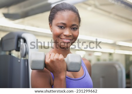 Fit woman smiling at camera holding dumbbell at the gym - stock photo