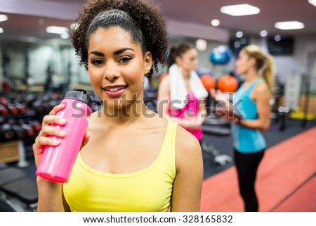Fit woman smiling at camera in weights room at the gym