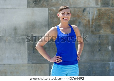 Fit woman smiling. Resting after run against the city wall.