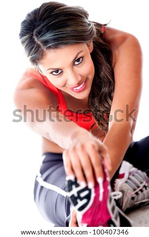 Fit woman stretching her leg - isolated over a white background - stock photo