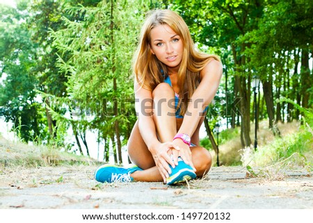 Fit woman stretching her leg outdoor - stock photo