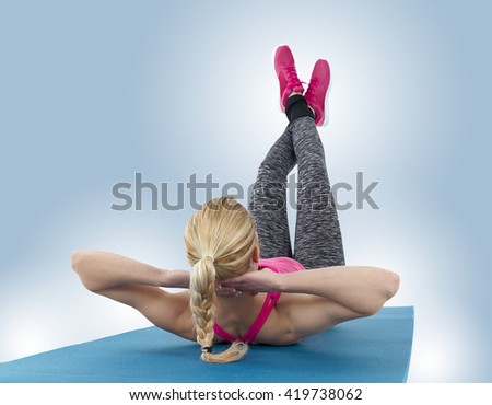 Fit woman stretching in fitness studio doing exercise abdominal crunches - stock photo