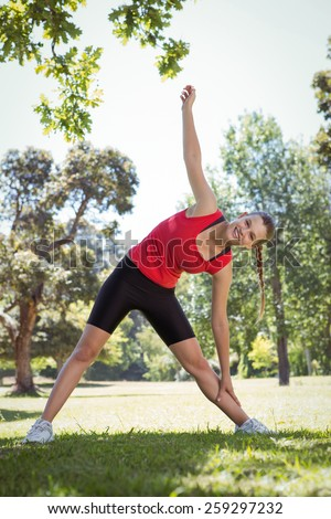 Fit woman stretching in the park on a sunny day - stock photo