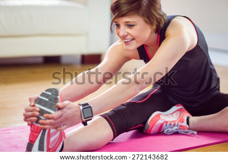 Fit woman stretching on exercise mat at home in the living-room - stock photo