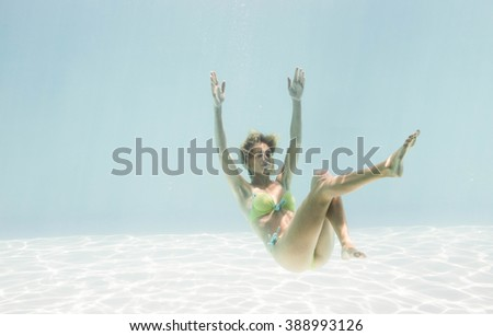Fit woman swimming under water in the pool