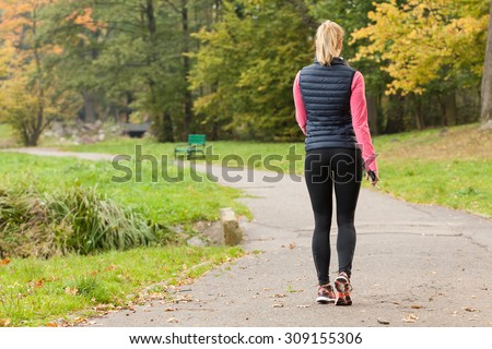 Fit woman walking in park during autumn time - stock photo