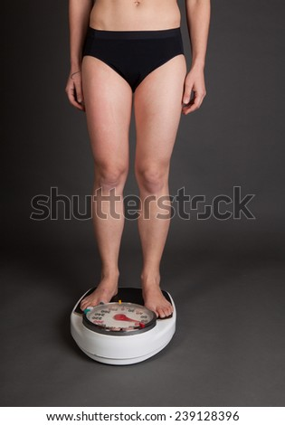 Fit woman weighing herself on a scale - stock photo