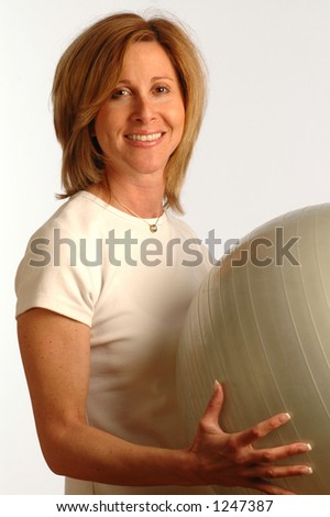 fit woman with smile using core training ball - stock photo