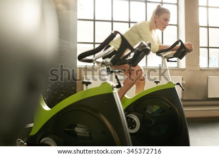 Fit woman working out on exercise bike at the gym. Indoor shot of a sportive woman doing fitness training on bicycle at health club. - stock photo