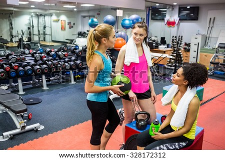 Fit women chatting in weights room at the gym - stock photo