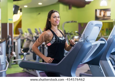 Fit women doing cardio exercises, running on treadmills in the gym - stock photo