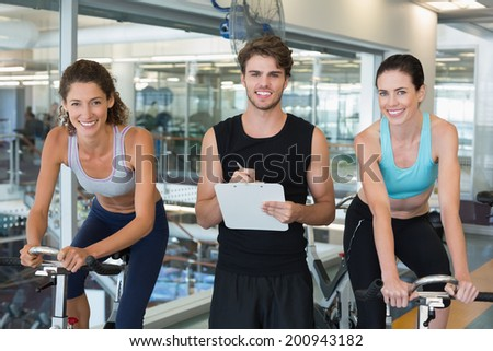 Fit women in a spin class with trainer smiling at camera at the gym