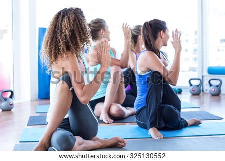 Fit women in fitness studio doing spine twisting pose on exercise mat - stock photo