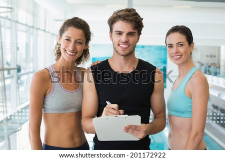 Fit women with trainer taking notes and smiling at camera at the gym - stock photo
