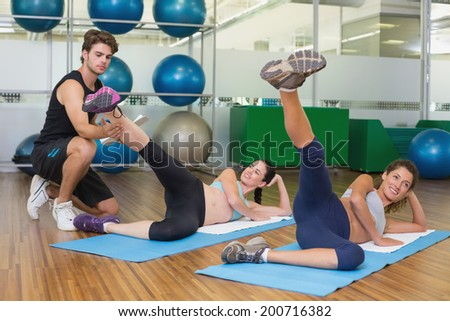 Fit women working out together in studio with trainer at the gym - stock photo