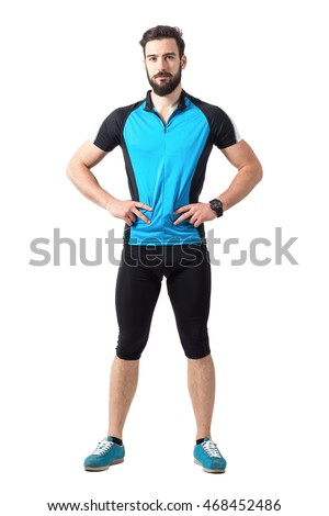 Fit young bearded athlete in cycling sportswear with arms on hips looking at camera.  Full body length portrait isolated over white studio background.