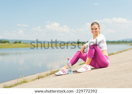 Fit young blonde Caucasian woman taking a break from jogging sitting by the lake. Attractive  teenage woman in pink tights relaxing after workout outdoors in summer. No retouch. - stock photo