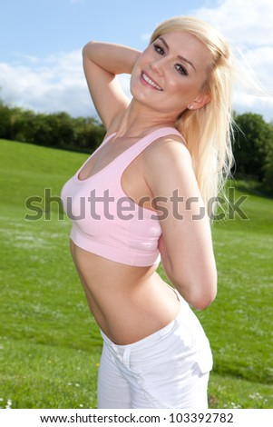 Fit young blonde woman in a pink top outside on a sunny day - stock photo