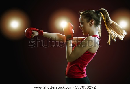 Fit, young, energetic woman boxing, black background, back light  - stock photo