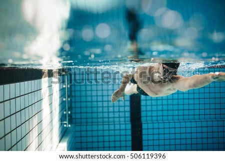 fit young male swimmer training in the pool pro male swimmer in action inside swimming - Inside Swimming Pool