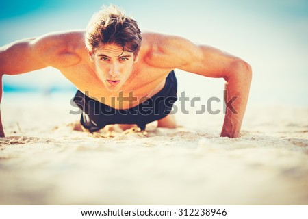Fit young man doing push-ups on beach. Outdoor beach workout. Handsome young fitness man exercising. Sports and active lifestyle fitness concept.  - stock photo