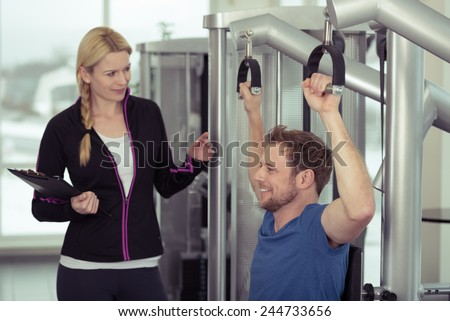 Fit young man working out with an attractive blond female trainer at the gym as they discuss his workout regime and progress in a health and fitness concept - stock photo