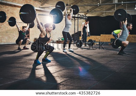 Fit young people lifting barbells over their heads looking focused, working out in a gym with other people - stock photo