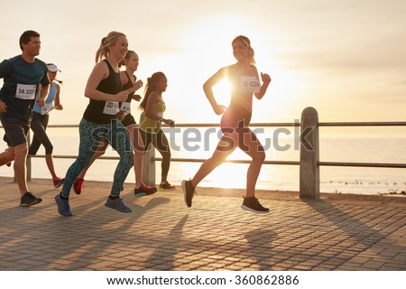 Fit young people running on street by the sea. Runners competing in a marathon race in evening. - stock photo