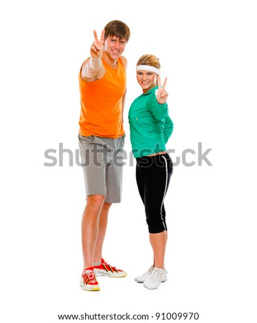 Fit young woman and man in sportswear showing victory gesture isolated on white - stock photo