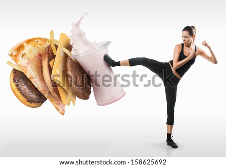 Fit young woman fighting off fast food - stock photo