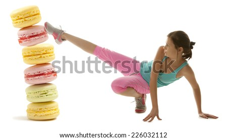 Fit young woman fighting off tasty colorful macaroon isolation on a white background - stock photo