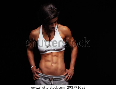 Fit young woman in sportswear looking down while standing with her hands on her hips. Muscular female model posing against black background. - stock photo