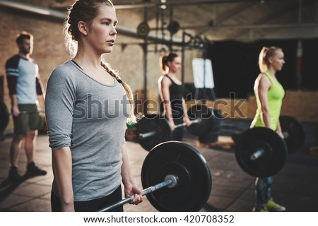 Fit young woman lifting barbells looking focused, working out in a gym with other people - stock photo