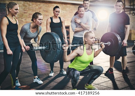 Fit young woman lifting barbells looking focused, working out in a gym with other people cheering her on - stock photo