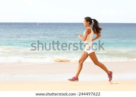 Fit young woman running along the edge of the surf on a sunny tropical beach in her sportswear with her long hair. Female runner exercising with copyspace - stock photo