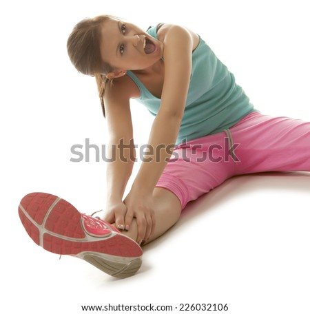 Fit young woman stretching her leg to warm up isolated  - stock photo